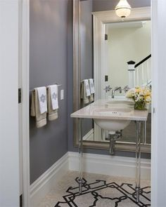 small gray blue powder room with blue purple walls paint color, beveled floor mirror, granite washstand with acrylic lucite base and mosaic tiles floor.