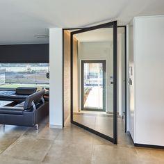Moderne stalen deur van Anyway Doors met pivotscharnier zonder inbouwelementen in de vloer.