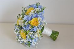 "Yellow roses, blue hydrangea, freesias, ""daisies"" ( Aster) and gypsophila make a gorgeous bouquet. *Replace daisy with orchid or babies breath"