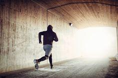 Aufnahme von hinten, vom einem jungen Mann beim Laufen.