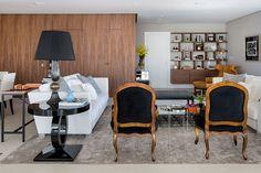 Sofá branco, cadeiras de madeira com estofado preto e paredes com revestimento de madeira.