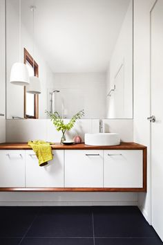 Wall hanging wood and white bathroom cabinet. Photo by Armelle Habib via Homelife. Pendant in the bathroom