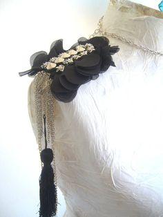 Un muy especial accesorio hecho con cadenas en tono plata, telas de la gasa negras, botones y borla. Es una joya para hacerte la estrella. Espero