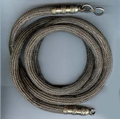Silver belt, crochet work creating hollow tube with silver end hooks worn wrapped twice. Oman early 20th c