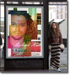 Tiger Lily Hutchence standing next to a poster of her Dad.Michael Hutchence