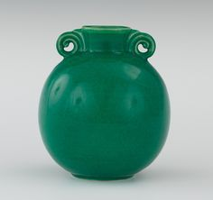"A Cowan Pottery Green Glazed Vase 6""H The orb-shape vase has a low neck with a flaring lip, flanked by scrolled handles, overall . 6""H, in a rich variegated clear green glaze, impressed mark on the underside. Rare vivid jade green color. Designed by Viktor Schreckengost for Cowan Pottery."