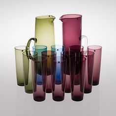 A set of 12 Tapio Wirkkala glasses, model 2204, and two jugs by Timo Sarpaneva and Erkki Vesanto. Iittala, Finland. Glasses in lilac, green and blue. Height 17.5 cm. Ten glasses labelled by Iittala. Lilac jug with handle in clear glass, designed by Timo Sarpaneva. Height 29 cm, manufacturer's label.  Green jug, model 2438, designed by Erkki Vesanto. Height 28.5 cm, manufacturer's label.