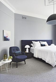 This bedroom features a white ceiling to contrast against grey walls and carpet. A striking textured navy bedhead paired with a matching navy armchair and dark grey pendant light add depth when contrasted with white sheets. Light Gray Bedroom, Gray Bedroom Walls, Navy Bedrooms, Grey Bedroom With Pop Of Color, Feature Wall Bedroom, Light Grey Walls, Bedroom Colors, Bedroom Decor, Master Bedrooms