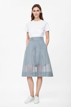 A clean, modern style, this sheer skirt is made from technical mesh fabric with a lightly padded quality and shorter poplin underskirt. Flaring towards the hemline, it has in-seam side pockets and a metal zip fastening that runs along the back.