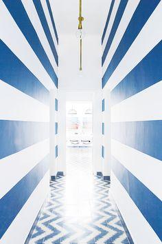 Tour a Pattern-Packed Coastal Bungalow in Morocco // blue striped walls, brass light fixture, chevron tiles, Popham Design, hallway Striped Hallway, Striped Walls, Narrow Entryway, Narrow Hallways, Entryway Ideas, Dark Hallway, Long Hallway, Hallway Walls, Chevron Floor