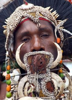 Papua New Guinea.  A Wewak tribal dancer, holding a traditional Karahut in his mouth | © Vincent Ross