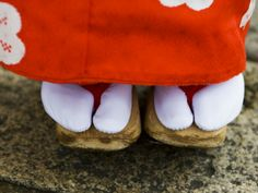 Feet and Dress of a Young Maiko - the toed socks are called tabi socks and the clogs type shoes are called zori.  These zori have a wooden botton but they can also be made of straw.
