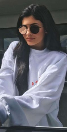 Who made  Kylie Jenner's black sunglasses, suede sneakers, and gray sweatshirt?