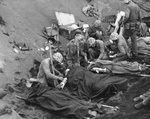 US Navy doctors and corpsmen administer to the wounded at a first aid station, Iwo Jima, Japan, 20 Feb 1945; Chaplain Lieutenant (jg) John H...