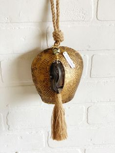 indian inspired gold bell with agate and tassel a beautiful gold floral etched bell that hangs from a natural jute cord this bell is adorned with a slice of agate in shades of black, a pretty bead and jute tassel rings with a medium tone bells are not only beautiful to look at but are known to