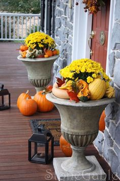 Urns overflowing with gourds and flowers are so welcoming on this front porch!