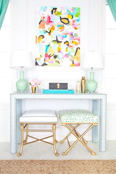 mismatched footstools + nailhead trim console + abstract art + twin lamps