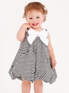 Your little girl will look adorable in a Biscotti Catch a Bow Bubble Dress in black and white. The dress features a traditional bubble shape with a large, voluminous skirt that tucks under towards the upper legs. The sleeveless design is accented with a large white satin bow at the neck that accents the smaller black and white striped bows and ribbons that are incorporated into the dress