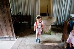 Sweetest boy wearing red braces, bow tie and a panama hat doing a jig at the church before a Herefordshire wedding © Babb Photo