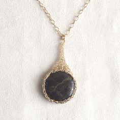 A unique Pyrite pendant necklace wire crocheted in unique shape that resembles a potion bag. The wire work is done in my trade mark, invisible spool knitting technique. Gold crystals like Pyrite are k