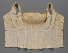 Stays | Museum of Fine Arts, Boston Lightly boned pair of stays in white cotton twill, top edge bound in same fabric, bottom edge bound in beige linen fabric, empty busk or steel casing down center front (interior stains), empty casings for baleen at back along lacing edges, pieced section at wearer's back lower left, all seams and lacing holes sewn with silk thread