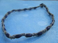 A classically simple hemp choker made with purple wood beads. Great for wearing to the beach or boardwalk! Approx. 15.5 in. long.
