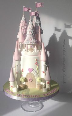 Beautiful princess castle cake. pink and purple castle cake with flags and garden details.