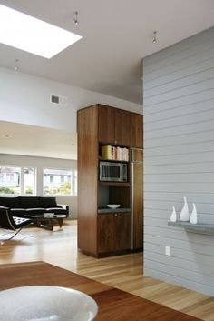 Contrast of dark and light wood... Tongue-and-groove plank installed on an entire wall can help delineate space within a space