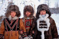 Three Evenk women dressed in traditional winter fur clothing. Kusur, Northern Yakutia, Siberia, Russia