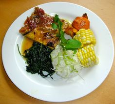 Angelica Kitchen ~    Grilled tofu in peach and plum marinade served with garlic sautéed spinach and nettles. Complemented by ginger scented jasmine rice, corn on the cob and roasted golden acorn squash
