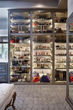 Stunning closet features a wall of lighted gray cabinets lined with sloped gray shelves filled with designer shoes, boots and bags finished with seamless glass bi fold doors.