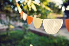 This scalloped paper bunting can be made for under two dollars, in about twenty minutes, in any color or size you'd like! In the time of a lunch break or a child's nap you can craft something beautiful for your next celebration.  The materials: A circular object to trace, scrapbook paper in whatever color or size you choose, a pen, scissors, double sided tape, and thread for hanging.