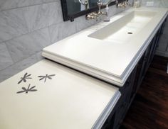 White concrete bathroom sink with steel dragonfly inlays fabricated by Trueform Concrete.  This was a fun way for the client to personalize their bathroom vanity tops. #TrueformConcrete #OurSinks
