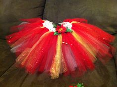 Handmade, custom Christmas tutu! This lovely red, gold & white tutu is embellished with a sparkly red poinsettia flower and green leaves. Two jingle bells dangle from the flower to add that extra special Christmas charm! The matching hair clip has the same sparkly red poinsettia and green leaves, along with the two little bells.  $25 for the set from Tabi's Tutus. Questions or orders can be placed by email at: t_dombach@yahoo.com