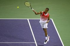 Nick Kyrgios Photos Photos - Nick Kyrgios of Australia returns a shot to Milos Raonic of Canada during the Miami Open presented by Itau at Crandon Park Tennis Center on March 31, 2016 in Key Biscayne, Florida. - Miami Open - Day 11