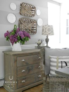 Loving the tobacco baskets, and three drawer chest. Great neutrals too, with a pop of purple.