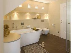 In Decke und Wandnische eingebaute Spots sorgen für eine warme, indirekte Beleuchtung. Das zwölf Quadratmeter große Badezimmer bietet genügend Raum für eine große Badewanne.