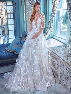 Arabella is a romantic voluminous dress that is made of layered silk tulle fabrics that come in delicate pink and ivory. It is entirely embellished with three dimensional silk flowers, crystals, beads and scattered silk petals that adorn the neckline. The dress has a full skirt and hidden pockets.