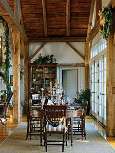 Antique English sconces glamorize the rough-hewn posts in the dining room of this Virginia country home. Garland and wreathes bring cozy Christmas cheer to this warm, sophisticated entertaining spot. (Photo: Antoine Bootz)