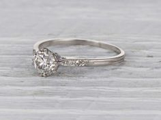 Antique Edwardian engagement ring made in platinum and centered with a .90 carat GIA certified old European cut diamond with I color and VS1 clarity. Circa 1920 Exquisite Edwardian craftsmanship featu
