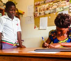 A Bujubuli teacher writes a student a note so he can have lunch, even though his tuition is not paid.  (Photo Credit: Rebecca Rwakabukoza)
