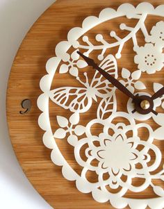 """Carved in the Japanese """"Kirie"""" style, this bamboo clock features an ornate design of butterflies and flowers lasercut out of white acrylic.   Etsy shop Decoy Lab."""