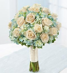 Two-dozen elegant white roses gathered with blue hydrangea and accented with red hypericum and variegated pittosporum creates a stunning complement to your wedding day ensemble.