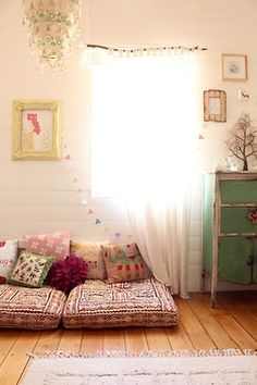 I love the shapes of the frames and use of wall space here. Colorful cushions on the floor.