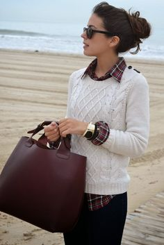 White cable knit sweater, red plaid button down shirt, brown bag, and gold accessories