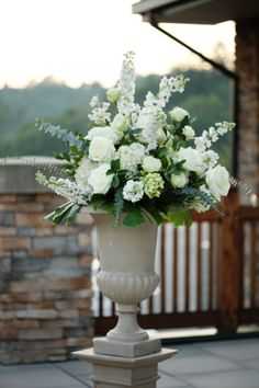 Urns with white flowers for your outdoor wedding.