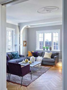 Også i stuen er flere originaldetaljer godt bevart. Guro og mannen er veldig glad i maleriet som er signert Brita Dagestad, og tok utgangspunkt i det da de skulle velge farger på møblene. Både sofaer og stoler er fra Fogia, de lilla stolene er trukket i et velurtekstil, huseier er glad i å blande ulike tekstiler. De oransje putene er fra HM Home, den blåmønstrede fra Balzac, gullputen er fra Missoni Home. Spotene i taket er en fin og subtil teknisk detalj og blir som en svevende kube i…