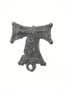 Pilgrim badge from St Antony's Hospital in Threadneedle Street, London. The badge is in the shape of a Tau cross (a T-shaped cross that resembles the Greek letter Tau). It is beaded around the edge and has a pearl at each outward corner. The cross is decorated with the figure of crucified Christ. Production Date: Late Medieval; 15th century