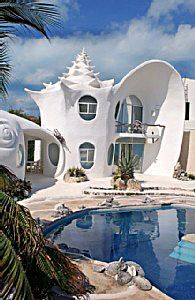 Casa Caracol ~ is a 3-story residence that has been featured on the Travel Channel. Its owner, architect and well-known Mexican artist Octavio Ocampos, designed it in the shape of a giant conch shell. Available for rent, as seen from the water it stands like a white stucco mirage shimmering in the tropical sun. #Isla_Mujeres #Casa_Caracol