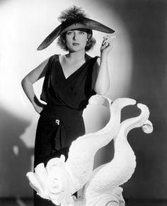 Carole Lombard con un vestido negro de tirantes y una pamela espectacular.